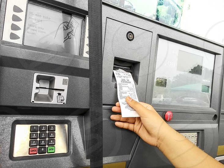Closeup of hand taking receipt of fuel pump machine at petrol station photo