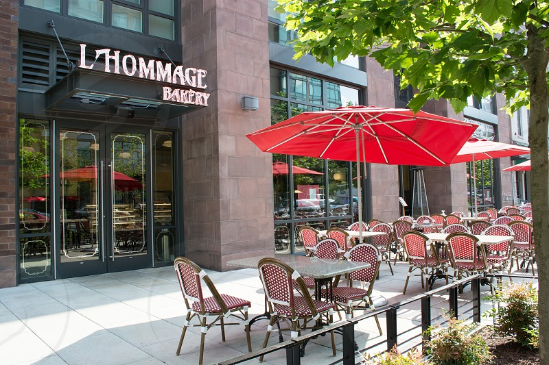 rectangular gray table with chairs and umbrella place outside L'Hommage Bakery facade photo