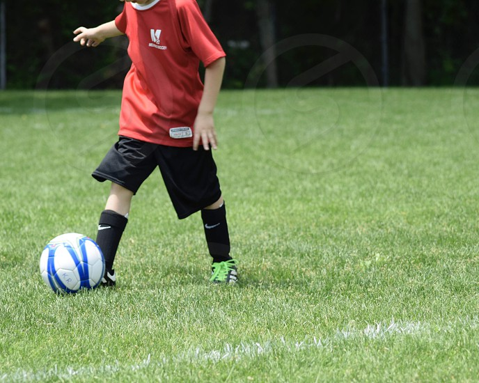 Kids competing over soccer ball photo