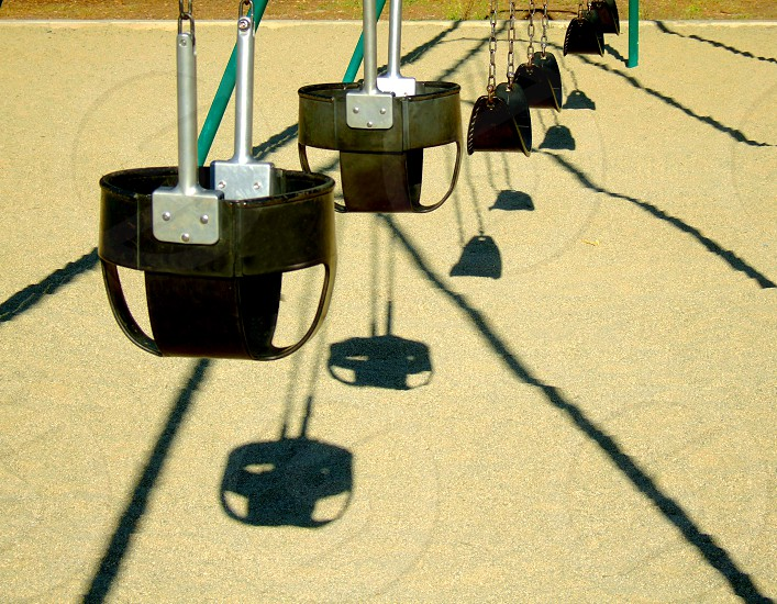 A row of toddler swings casts a pattern in the sand in the park photo