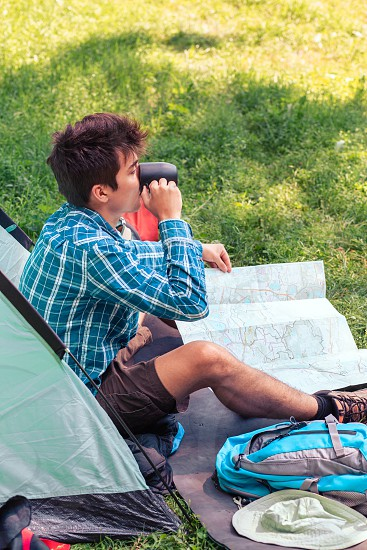 Spending a vacation on camping. Young man planning next trip and drinking a coffee photo