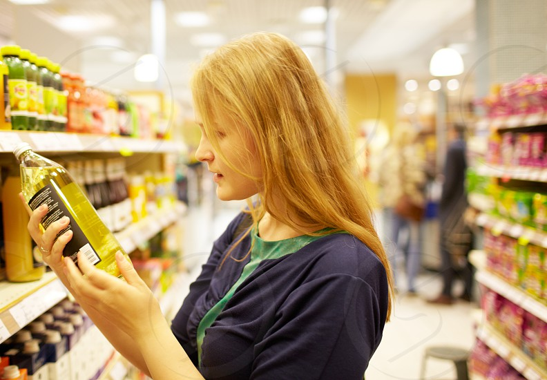 Young blonde woman in the supermarket is reading inscription on the juice bottle photo