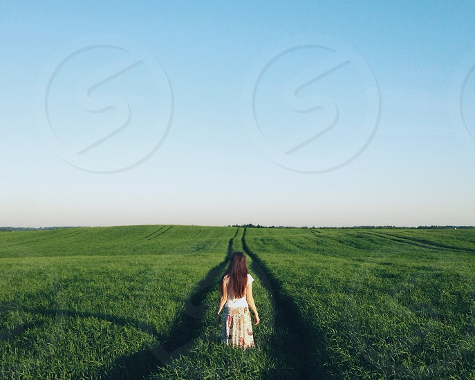 back of a brunette woman in a skirt standing in a green grass field with tractor tire cutouts photo