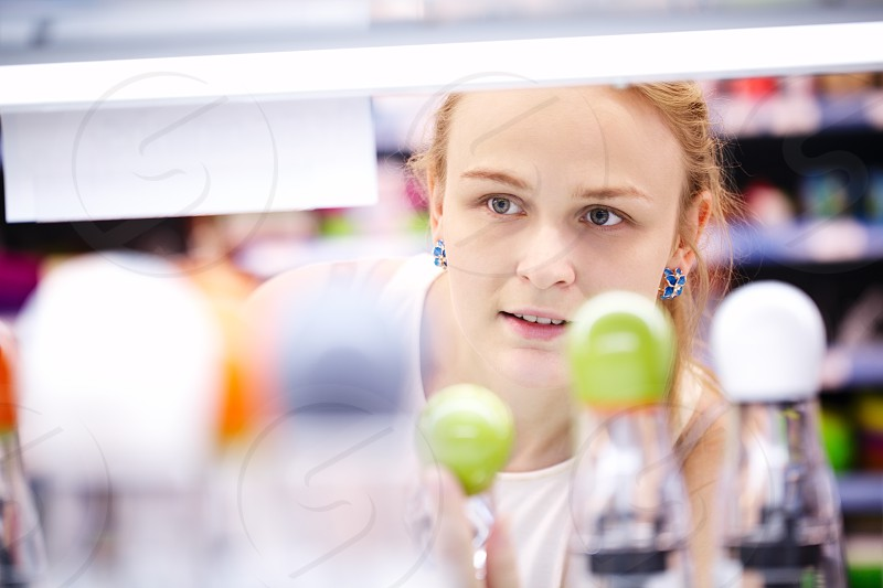 Young blond woman carefully analyzing products in a store - view through products photo