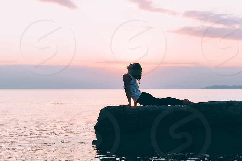 Young woman doing yoga by the sea photo