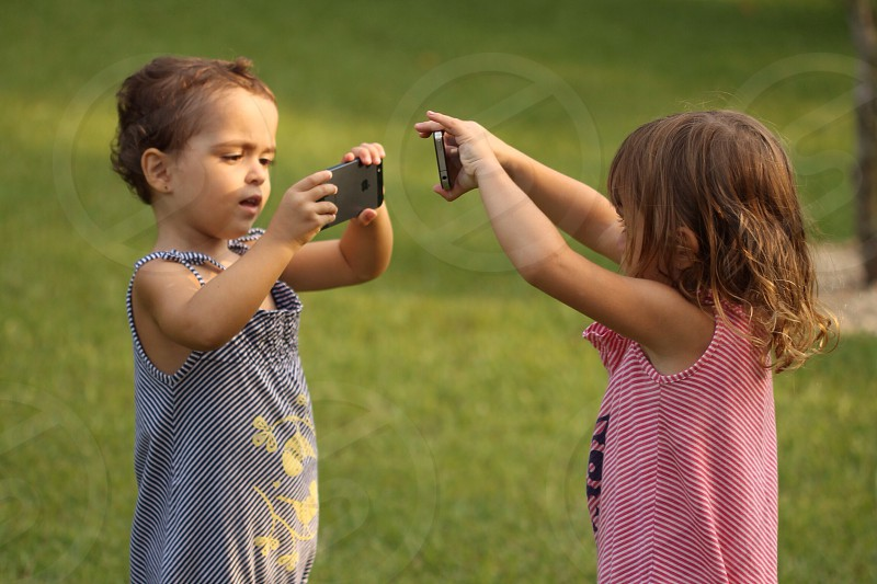 2 girls face to face taking picture to each other photo