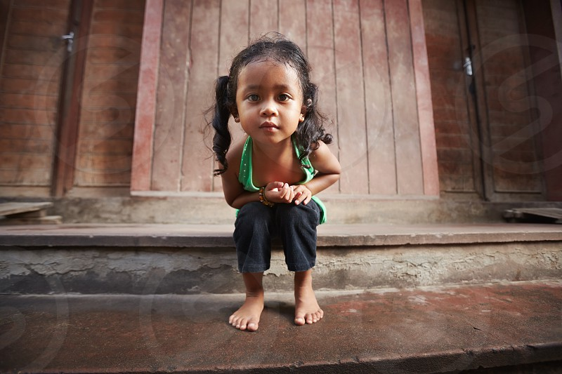 staring; portrait; asian; barefeet; child; childhood; children; young; 5-6; alone; asia; barefoot; beautiful; cambodia; cambodian; casual; curious; curiosity; cute; emotions; expression; female; front view; full length; future; girl; little; lonely; looking; camera; looking at camera; one; outdoors; people; person; posing; pretty; real people; sitting; southeast asia; space; stare; street; t-shirt; wall; woman; years; youth photo