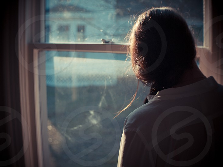 Young woman reflecting on life. vintage house young woman light window hair brunette moody dreary reflections photo