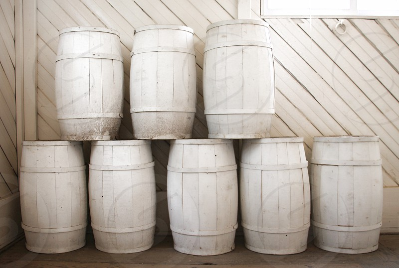 Eight white painted barrels are stacked inside a white barn photo