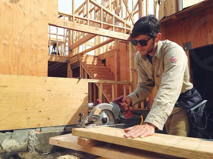 man sawing wood photo