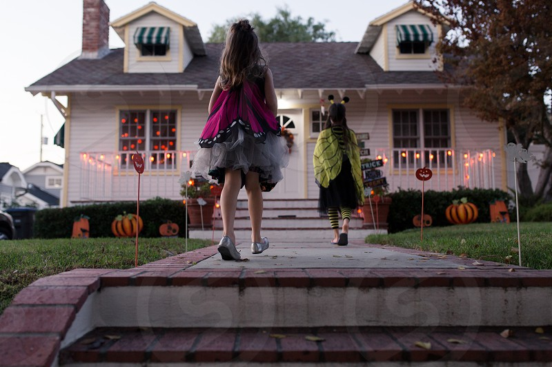 Sisters are trick or treating on Halloween. photo