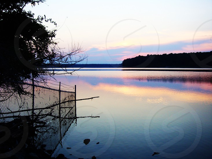 Fence and lake sunset reflection photo