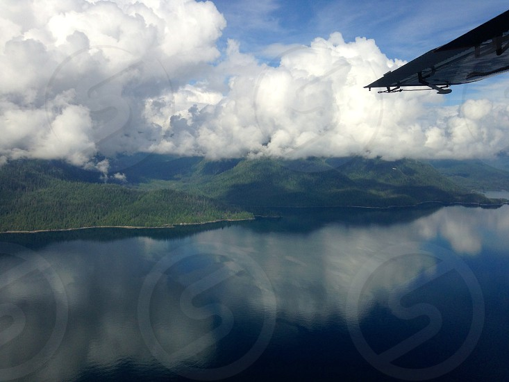 Mountains plane private jet clouds fog foggy aerial point of view Alaska United States travel winter cold contrast color definition wing trees nature landscape forest reflection lake water.  photo