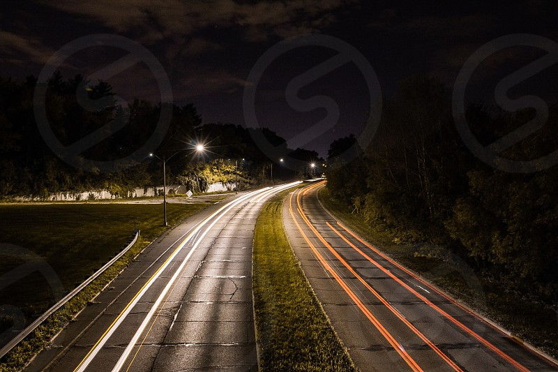 grass parcel between two parallel concrete roads with trees beside during night time photo