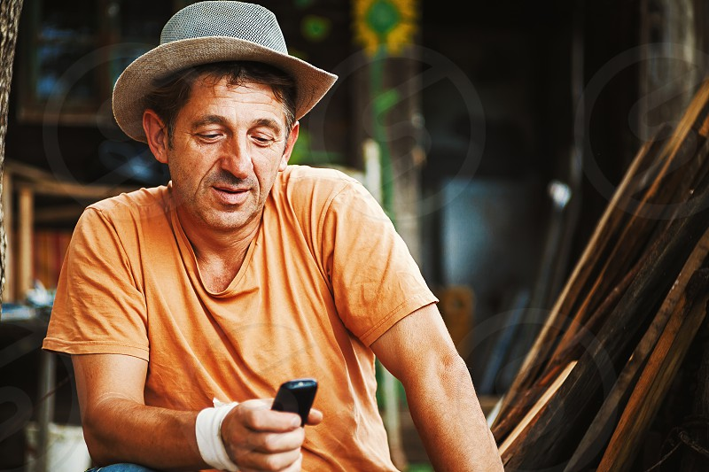 Portrait of an ordinary country man in Serbia working and communicating with mobile.  photo