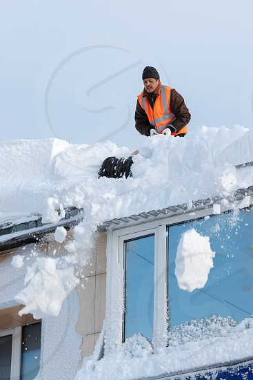 PETROPAVLOVSK KAMCHATSKY CITY KAMCHATKA RUSSIA - DEC 27 2017: Worker with snow shovels carry out cleaning of roof of residential building from snow and ice after heavy winter snow cyclone blizzard photo