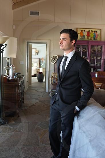 man in black suit standing photo