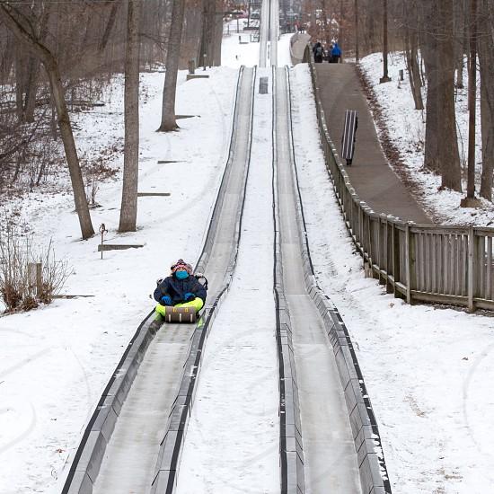 A family riding a toboggan in winter photo