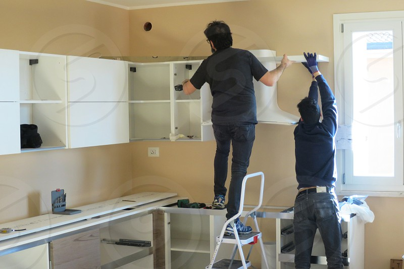 carpenters workers install new kitchen after the move photo