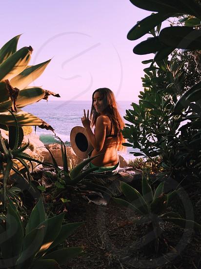 woman wearing bikini top sitting near green leaves and body of water under blue sky photo