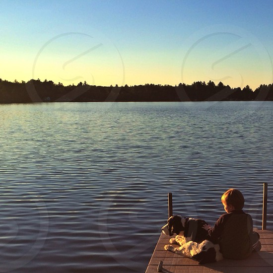 boy sitting on lake dock photo