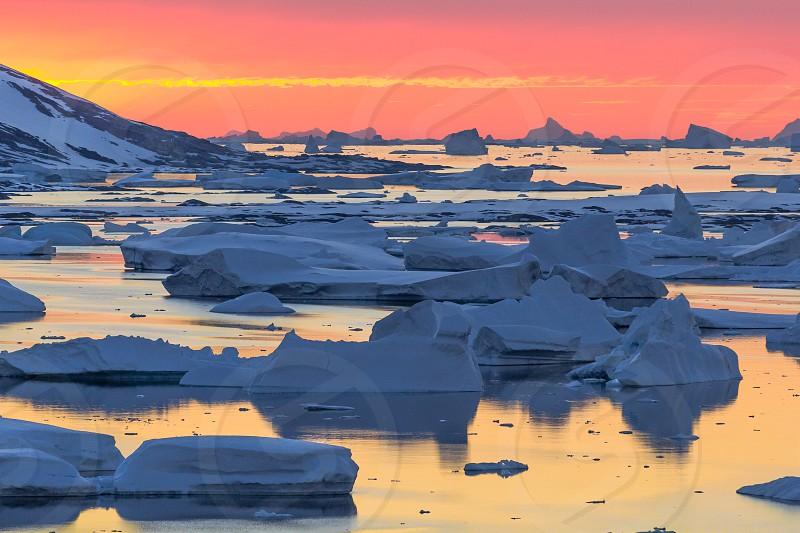 Antarctica peninsula Port Charcot sunset reflection colors magical iceberg sun stream ocean adventure exploring expedition hiking cold photo