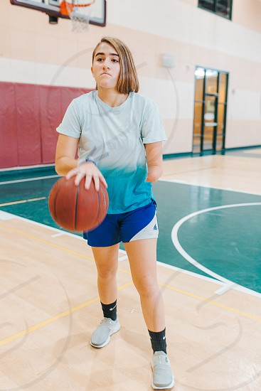 Girl who is missing her forearm playing basketball photo