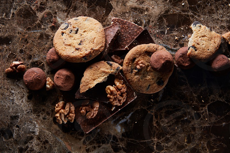 Fresh homemade chocolate chip cookies with chocolate candies in the dark marble background. photo