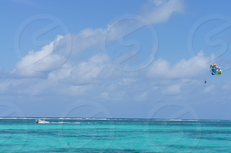 multicolored balloons flying over blue ocean water photo