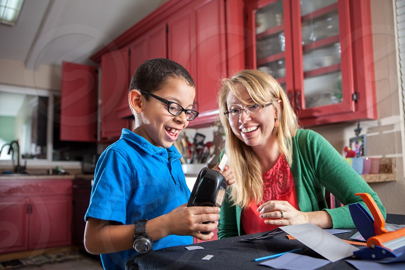 An actual diverse foster home passionate about fostering adopting loving teaching children who need a forever family. Black white mixed race happy learning kitchen table cloth blue green red glasses boy woman relating connecting together diversity. Arts and crafts. photo