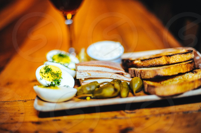 sliced boiled eggs near sliced toasted breads near clear wine glass photo