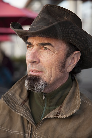 Man facial hair cowboy hat work clothes earthy looking to the left lost in thought photo