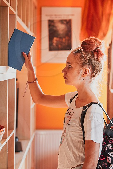 Teenage girl looking for books in local library. Young woman with a backpack standing by a bookshelf indoors. Real people authentic situations photo