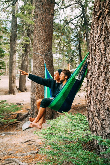 couple in green and black hammock under green tree at daytime photo