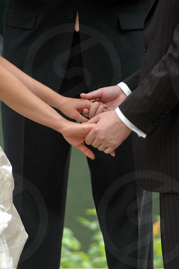 A bride and groom holding hands during their wedding ceremony photo