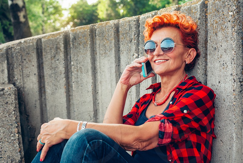 Hipster mature woman is calling via cell telephone while sitting in the fresh air in warm spring day gorgeous female is talking with her friend via mobile phone while resting in park outdoors photo