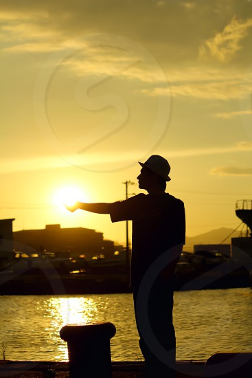 silhouette of man beside sea pointing photo