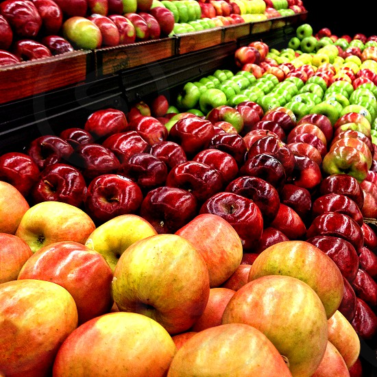 Apples of different varieties extend from foreground to background in a grocery store. photo