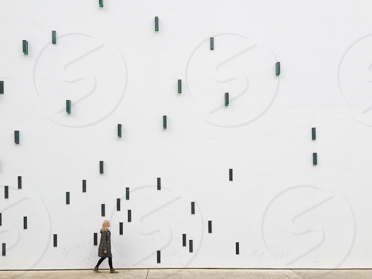 blond woman in black cold weather coat walking past tall white wall with black rectangles installation photo