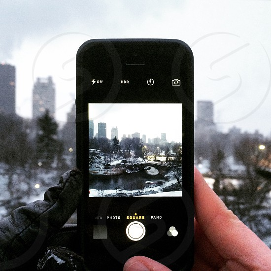 person capturing a photo of lake surrounded by trees photo