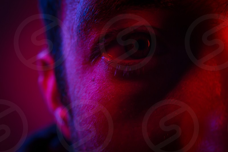 Close up on man face with mysterious facial expression. Portrait of suspicious young man. photo