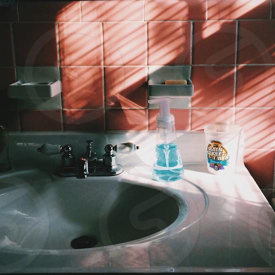 blue bottle near faucet photo