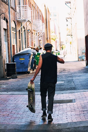 man in black tank top carrying skateboard while walking on road photo