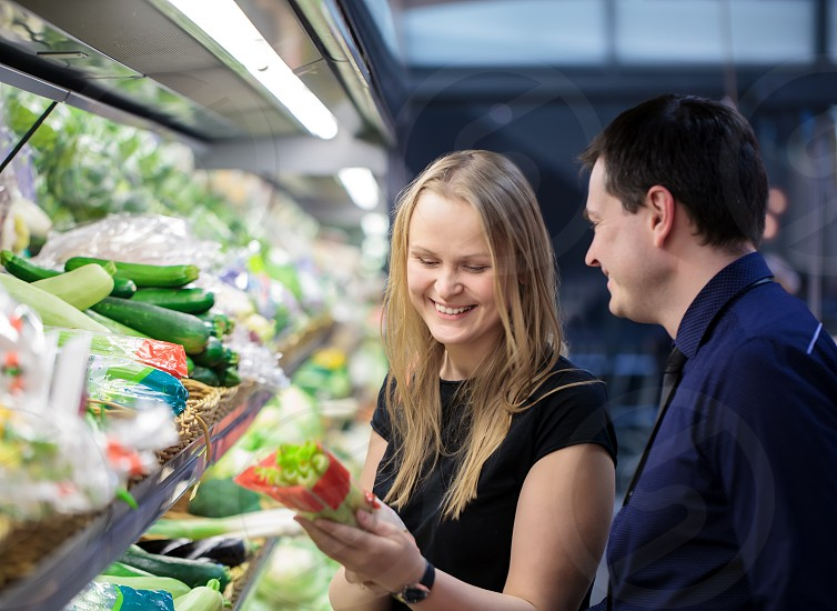 Man and woman shopping for vegetables at the grocery photo