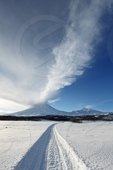 Winter landscape of Kamchatka: snowmobile track to eruption active Klyuchevskoy Volcano (Klyuchevskaya Sopka) - emission from crater of volcano plume of gas steam and ashes. Eurasia Russian Far East Kamchatsky Krai. photo