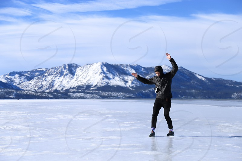 person wearing black leather jacket standing on icy surface beside a white and gray rocky formation mountain full of snow during winter season photo