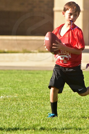 boy score touchdown playing football photo