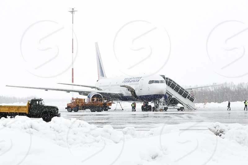 PETROPAVLOVSK-KAMCHATSKY KAMCHATKA RUSSIA - MARCH 19 2015: Service and technical support airfield maintenance airplane Boeing-767 Transaero Airlines at airport of Petropavlovsk-Kamchatsky (Elizovo airport) at the time of bad weather (snowfall). photo
