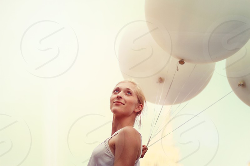 woman in white spaghetti strap tank top holding 3 white balloons photo