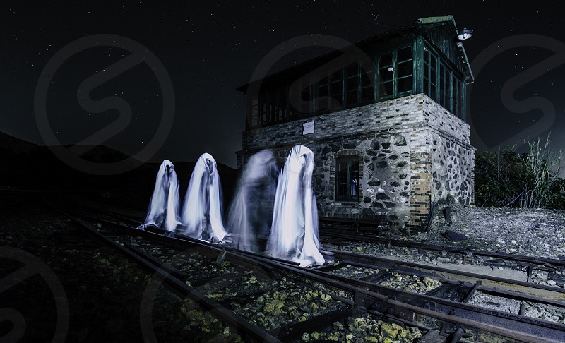 Four ghosts walking on the train track in front of the house photo